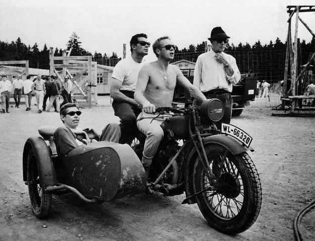 01 Nov 1962, Munich, West Germany --- Between takes on the film , Steve McQueen in the driver's position on a motorcycle with James Garner behind him and James Coburn in the sidecar, about to roar through nearby Munich, West Germany. --- Image by © Bettmann/CORBIS